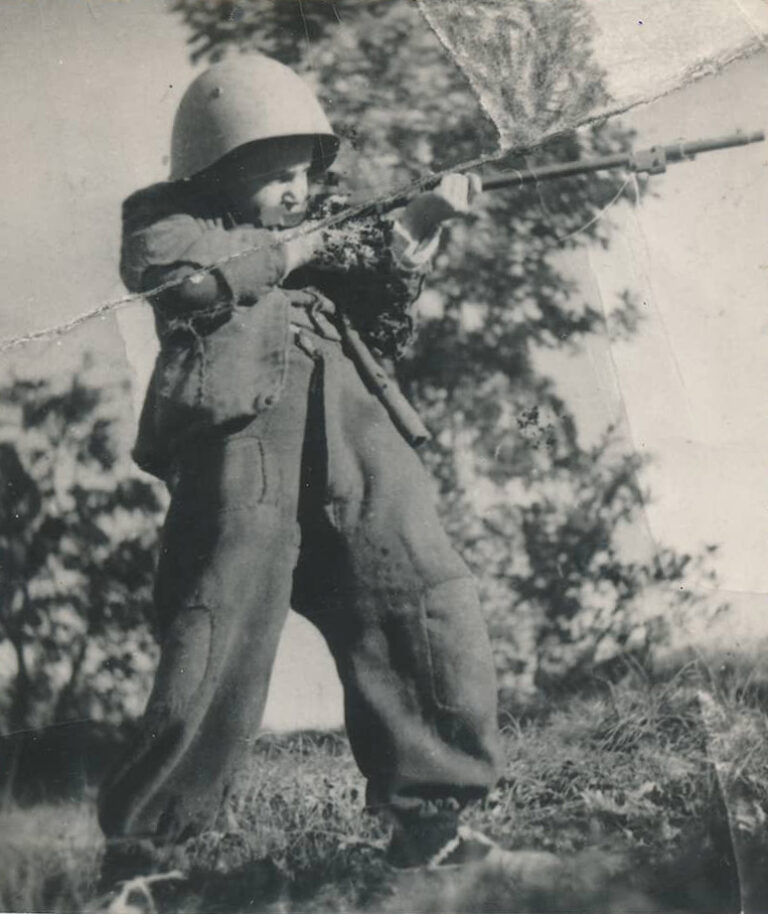 Child posing as a soldier, April 1944